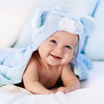 smiling baby wrapped in a blue towel