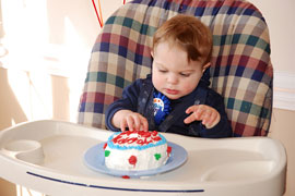 baby in high chair with birthday cake